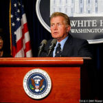 Martin Sheen as Jed Barlet standing at the podium with Presidential seal