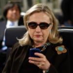 Hillary Clinton seated on a plane, looking at her cellphone, wearing sunglasses.