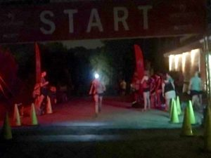 Runner with headlamp crossing finish line