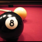 eight ball in foreground, cue ball behind with cue lining up on left