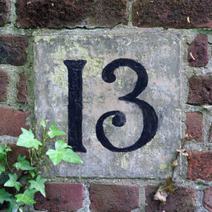 Number 13 in black against concrete surrounded by red brick