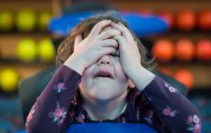 Young girl with hands covering her face and an expression of despair
