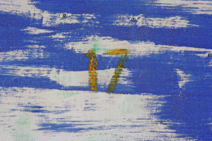 The number 17 painted in yellow against a blue and white background