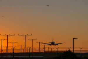 plane landing on runway at sunset surrounded by power lines