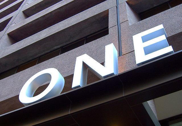 The letters O N E diagonally from lower left to upper right corner against a dark background of a building.
