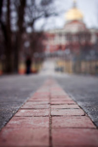 brick path with pavement o either side. blurry building far ahead