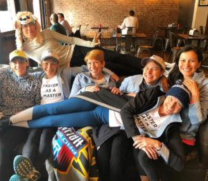 7 women piled on a couch, tired and happy