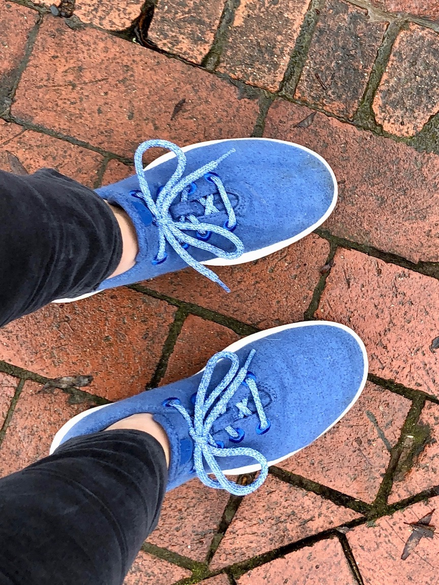 Blue tennis shoes against a brick sidewalk